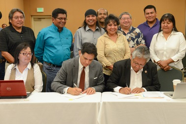 Terry Rambler (right), Chairman Of The San Carlos Apache Tribe, And Eduardo Pagan, ASU Vice Provost Of Academic Excellence And Inclusion, Sign An Agreement To Bring A College To The Tribal Nation As Members Of The San Carlos Apache Tribal Council Watch. Photo Courtesy ASU
