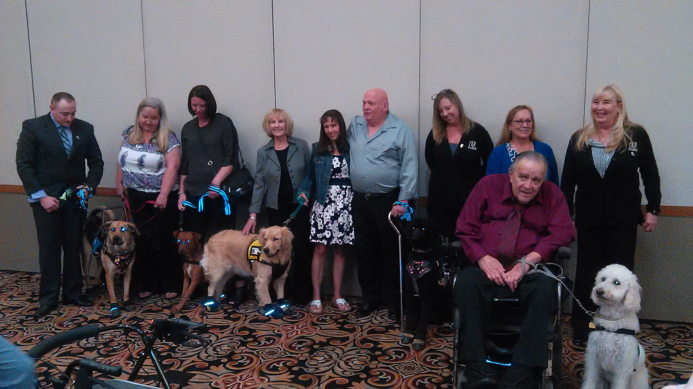 The Newly-minted Service Dogs Pose With Their New Owners, Who Will Rely On The Dogs To Help Them Recover From A Variety Of Mental And Physical Ailments. C.J. Betancourt Is Standing In The Middle, Wearing The Flower Dress And Jean Jacket. AAEC's Assistant Director Suzanne Drakes Is Third From The Right In The Black Sweater And AAEC Executive Director Linda Downing Is The Last Person On The Far Right, Also Wearing A Black Sweater.