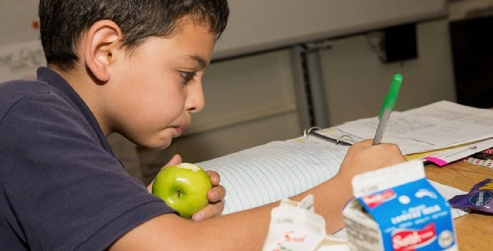 A Student Eating Breakfast In The Classroom As He Does Some Bell Work. Photo Courtesy Of Valley Of The Sun United Way