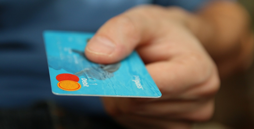 Hand Holding A Debit Card. Photo Courtesy Of Pixabay