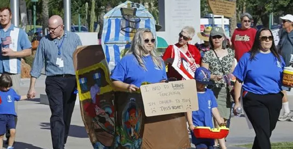 "Former Teacher Mary MacKay With Son Cameron March Along With Leah Knaeble At The State Capitol Wih Their ""boards"" That They Have Bought With Money From Second Jobs On May. 2, 2017 In PHoenix. Their Boats Were A Jab At A Recent Comment From A State Legislator. Photo Courtesy David Kadlubowski/The Arizona Republic"