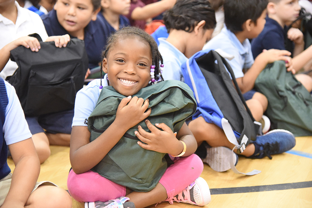 Thew Elementary Student Smiles With Her New Backpack