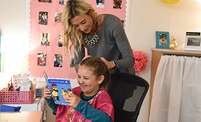 "Hudson Elementary First-Grader Gabriela Arevalo Reads A Book As Teacher Sarah Shipe AKA ""Sarah"" The Hair Dresser Braids Her Hair Before School. Photo Courtesy Tempe Elementary School District"