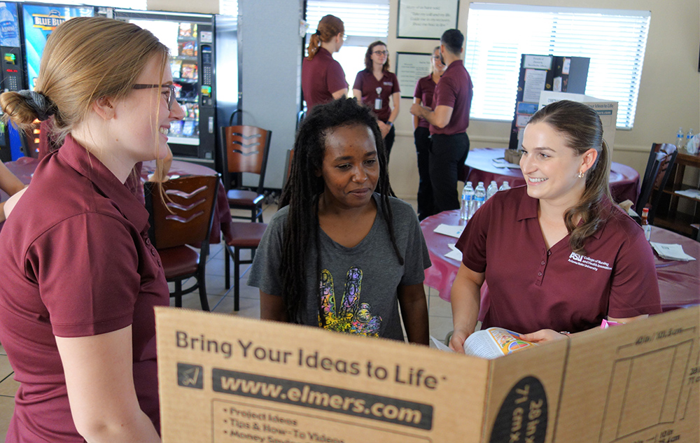 ASU Nursing Students Sienna Yturriaga (left) And Madeline Aaron (right) Discuss Healthy Eating With Crossroads Flower Resident Maza Wasi At A Student-run Health Fair At The Facility On June 11, 2019. Photo Courtesy Arizona State University's College Of Nursing And Health Innovation