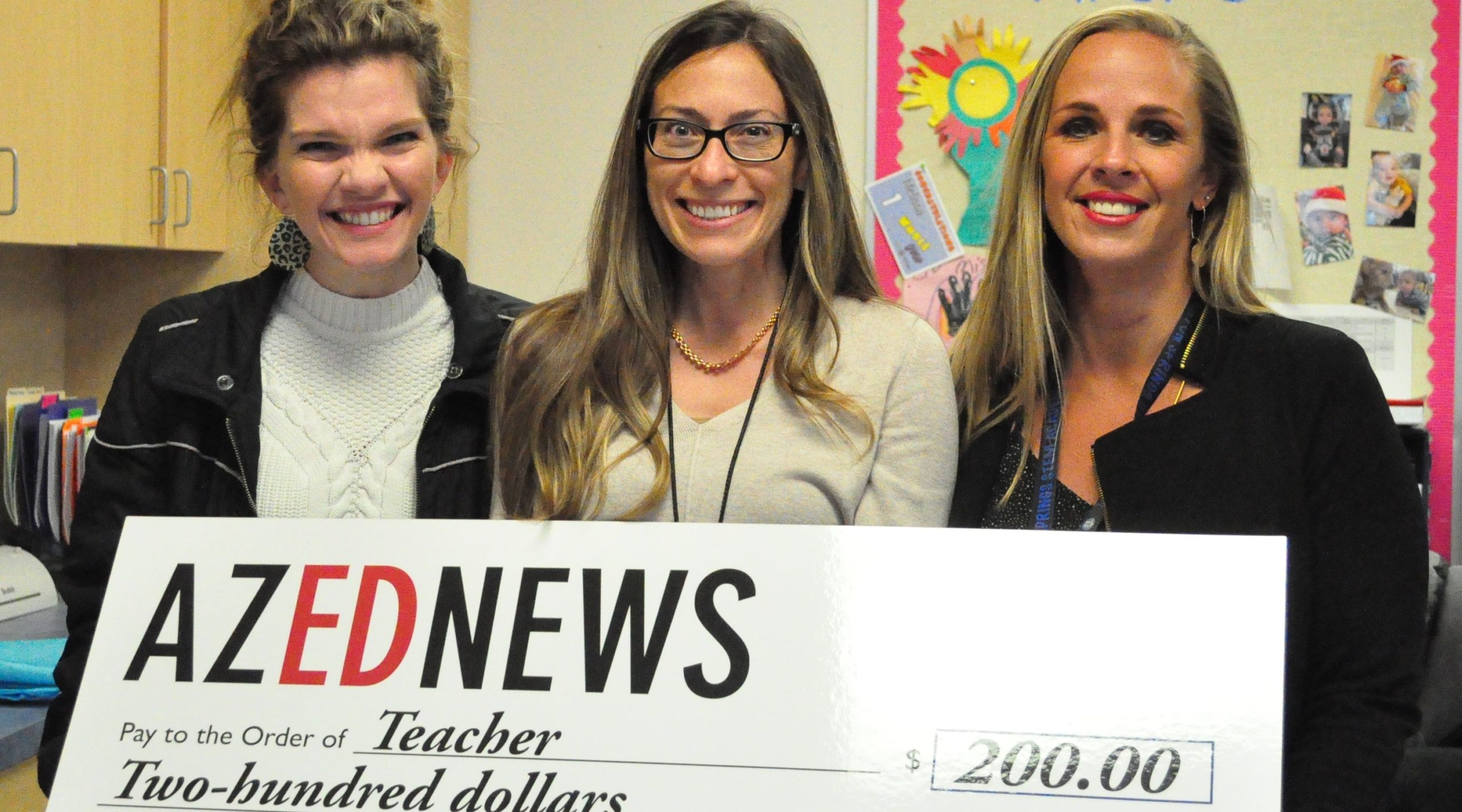 Canyon Springs Special Education Teacher And Student Support Services Coordinator LaRae Klay, Center, Accepts The AZEdNews Teacher Classroom Grant Check From Canyon Springs STEM Academy Assistant Principal April Fraley, Right. Photo By Lisa Irish/AZEdNews