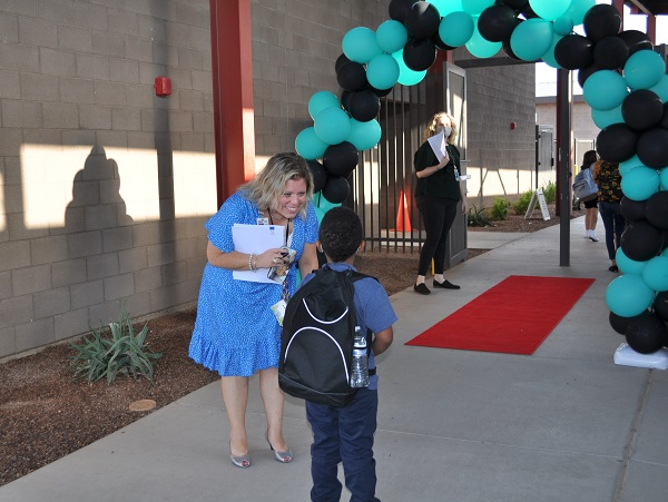Students head back for first day of school as COVID cases surge Principal-Foye-greets-a-student-600