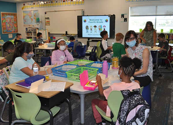 Students head back for first day of school as COVID cases surge Supt-Kathy-Hoffman-visits-with-students-in-classroom-600